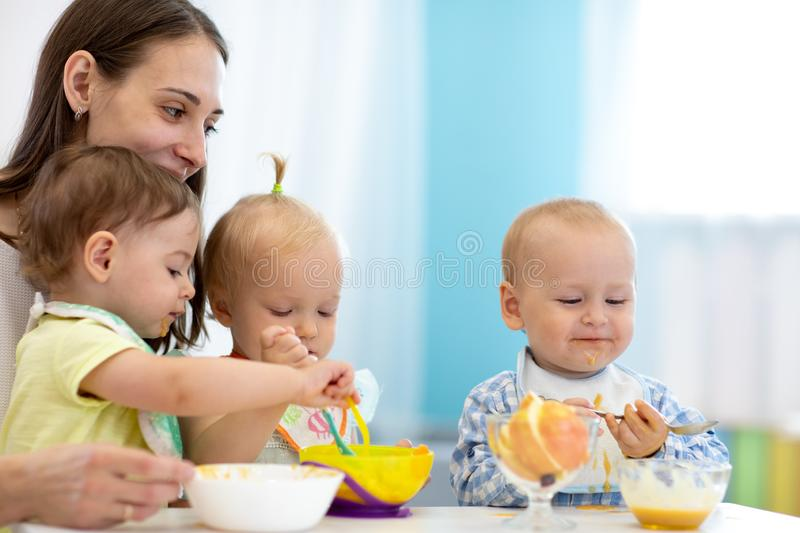 Group of nursery babies eating healthy food with babysitter help. Lunch break in creche. Time to eat in daycare royalty free stock photography