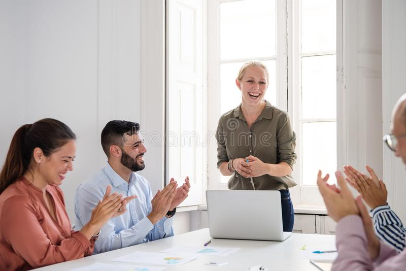 Group of office colleagues laughing and clapping. Successful group of office colleagues laughing and clapping motivated for the women in a green shirt stock image