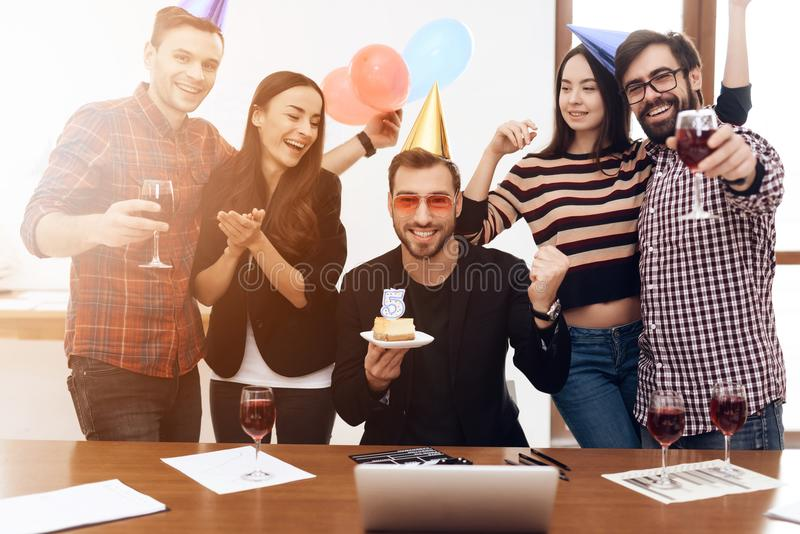 A group of office employees celebrate the fifth anniversary of their company. They are dressed in holiday caps. They are smiling stock image