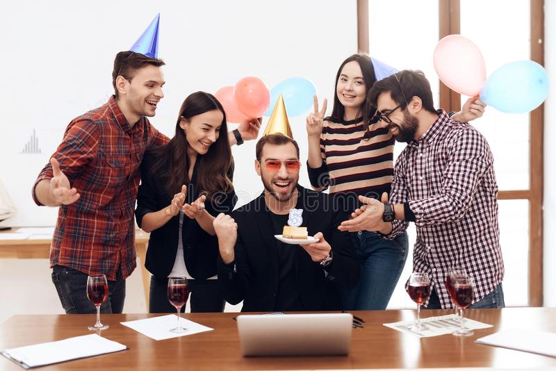 A group of office employees celebrate the fifth anniversary of their company. They are dressed in holiday caps. They are smiling stock photo