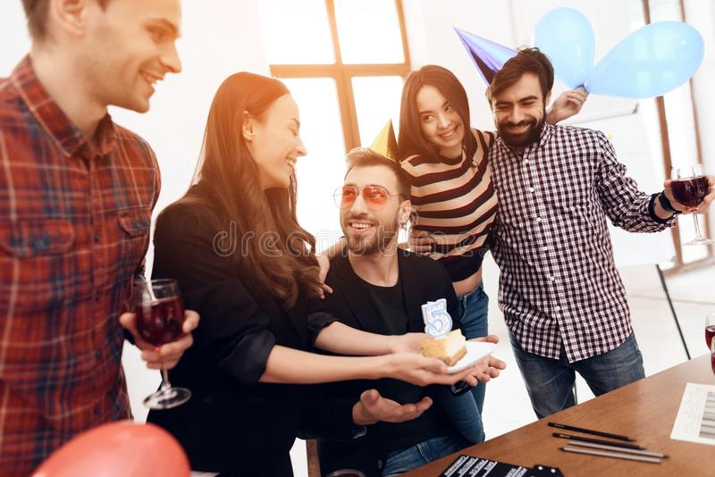 A group of office employees celebrate the fifth anniversary of their company. They are dressed in holiday caps. They are smiling stock images