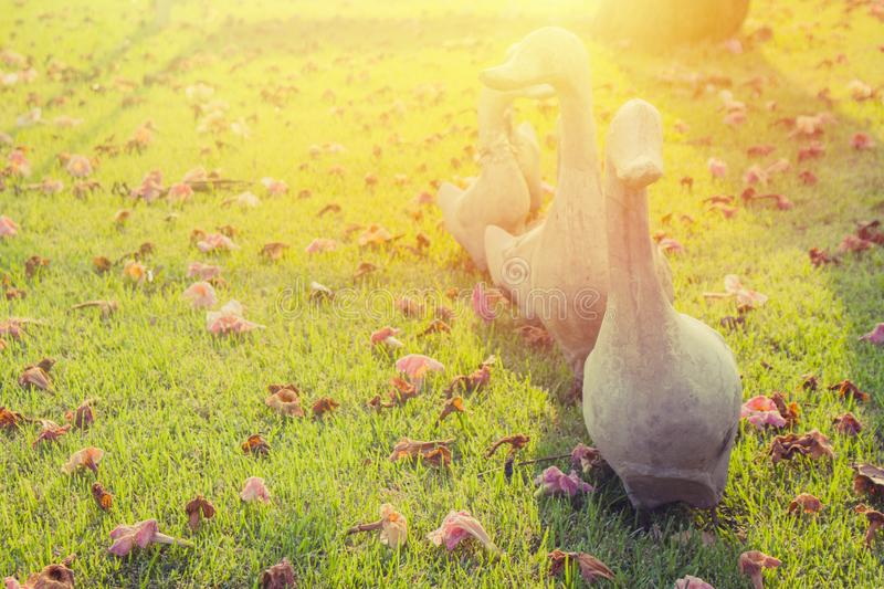 Group of old white ducks sculpture or stature standing on green grass meadow field . Group of old white ducks sculpture or stature standing on green grass stock image