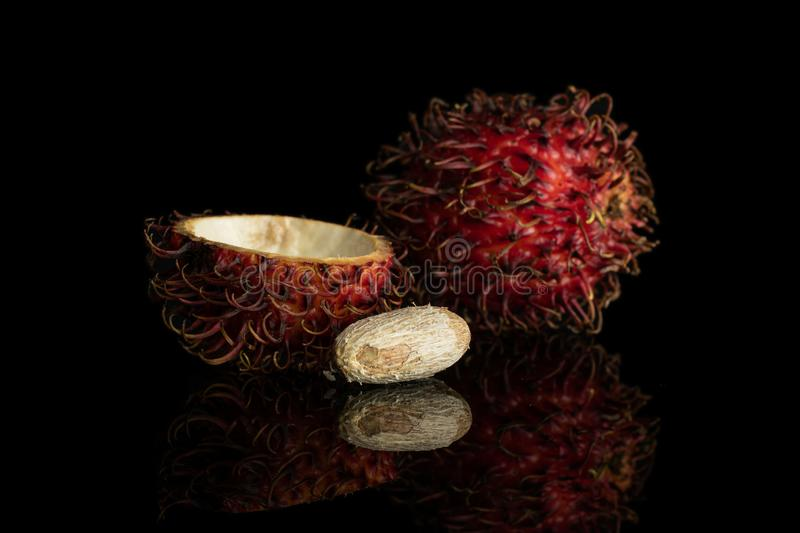 Fresh red rambutan isolated on black glass. Group of one whole one half one piece of fresh red rambutan isolated on black glass stock photos