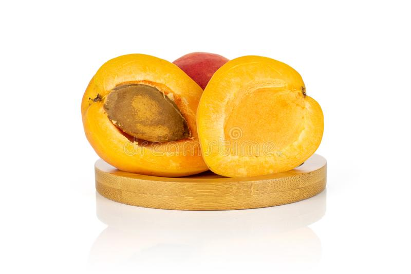 Fresh orange apricot isolated on white. Group of one whole two halves of fresh orange apricot with an apricot stone on a round bamboo coaster isolated on white stock image