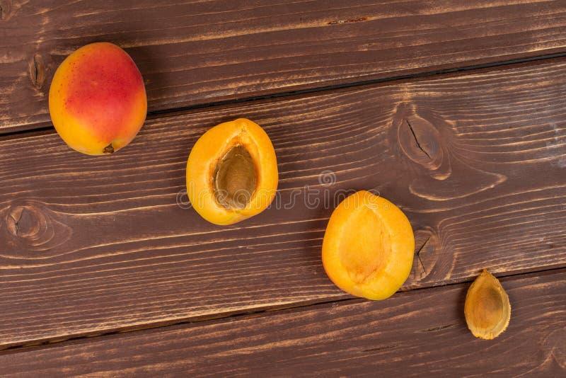 Fresh orange apricot on brown wood. Group of one whole two halves one piece of fresh orange apricot with an apricot stone flatlay on brown wood stock photo