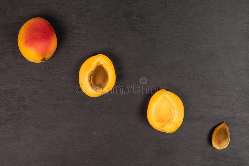 Fresh orange apricot on grey stone. Group of one whole two halves one piece of fresh orange apricot with an apricot stone flatlay on grey stone stock image