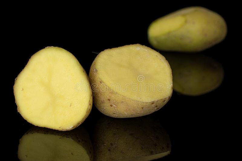 Raw brown potato isolated on black glass. Group of one whole two halves of raw brown potato isolated on black glass royalty free stock photography
