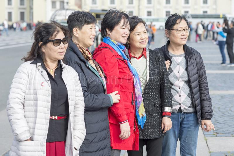 Group of Oriental women, tourists from Asia posing for photos at the Palace square of St. Petersburg, Russia, 2018 royalty free stock images