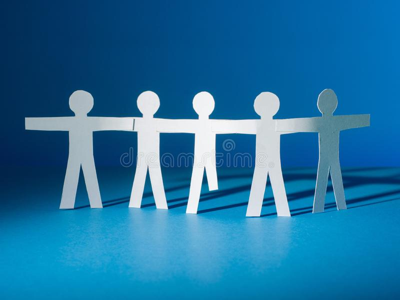 A group of paper people silhouettes stand together. One of them is disabled royalty free stock photo