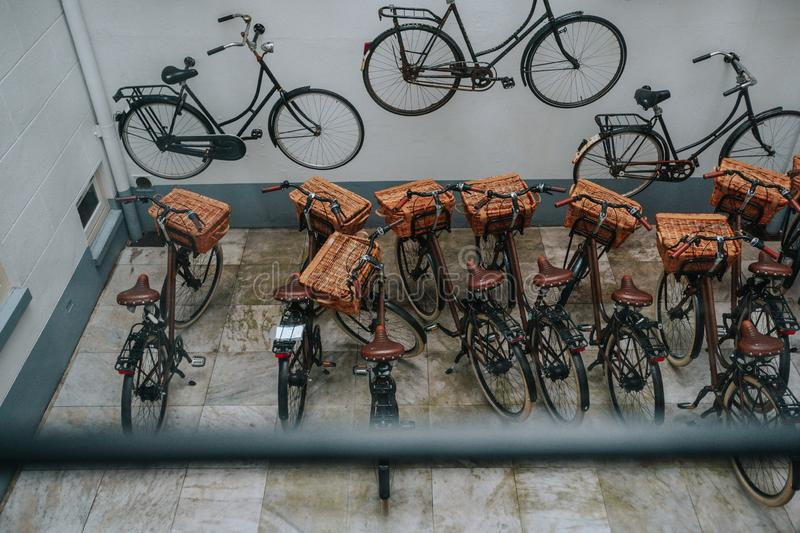 The group parked the bikes at the house. View from the window of a parked group of bicycles at the house with a white facade decorated with real bikes royalty free stock image
