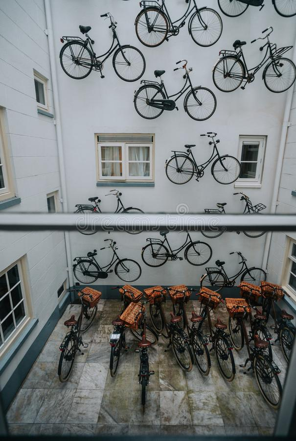 The group parked the bikes at the house. View from the window of a parked group of bicycles at the house with a white facade decorated with real bikes royalty free stock photos