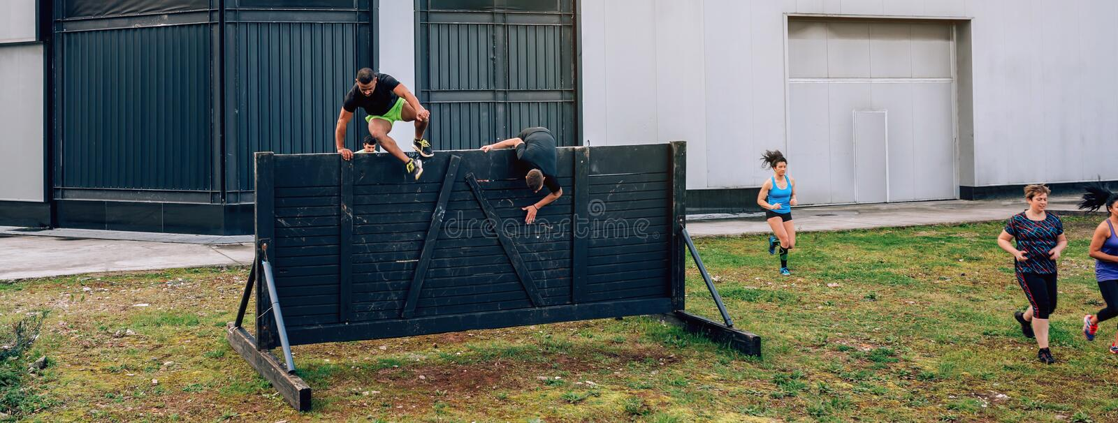 Participants in obstacle course running and climbing wall. Group of participants in an obstacle course running and climbing a wall stock photography
