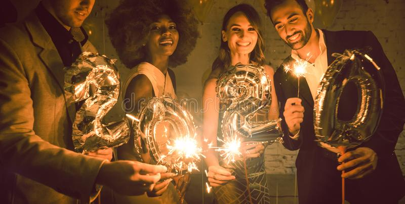 Group of party people celebrating the arrival of 2020 royalty free stock image