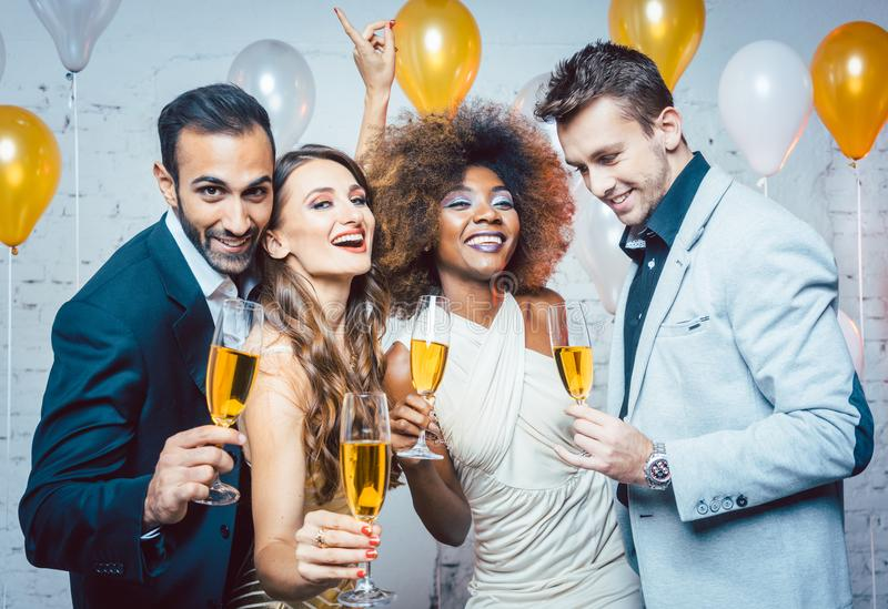 Group of party people celebrating with drinks royalty free stock photography