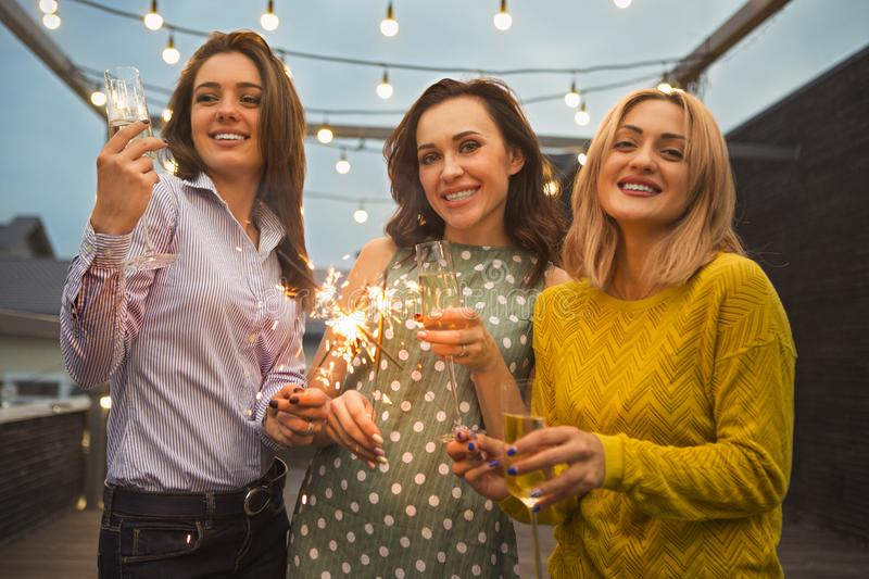 Group of partying girls with flutes with sparkling wine and bengal fire stock photography