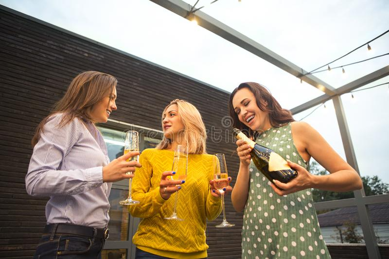 Group of partying girls with flutes with sparkling wine having fun royalty free stock photo