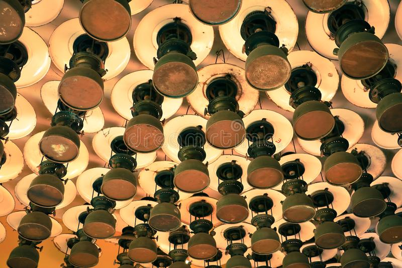 Group of pattern of old vintage storm lanterns, hurricane lamp hang on ceiling wood. Vintage lamp concept stock photo