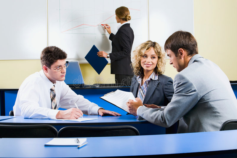 Group of people. Sitting at the blue table and discussing business questions in the class room stock image