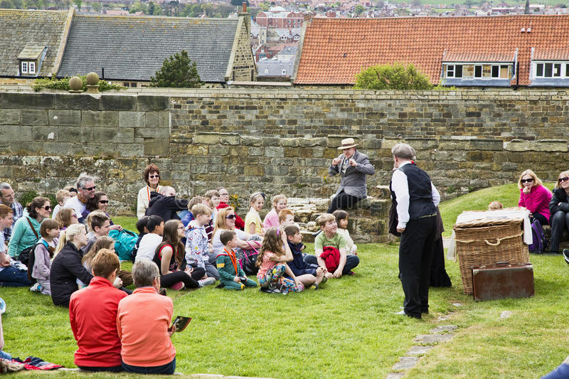 Group of people at Abbey ruins above whitby town. Children and adults listening to a Storyteller at the Abbey ruins on top of cliffs above Whitby Town telling a royalty free stock image