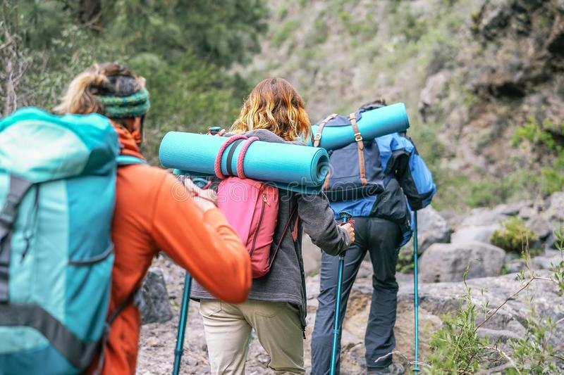 Group of people with backpacks doing trekking excursion on mountain - Young  tourists walking and exploring the nature royalty free stock photography