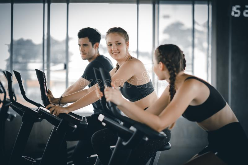 Attractive woman biking in the gym, exercising legs doing cardio workout cycling bikes. Fitness club with training exercise bikes royalty free stock image