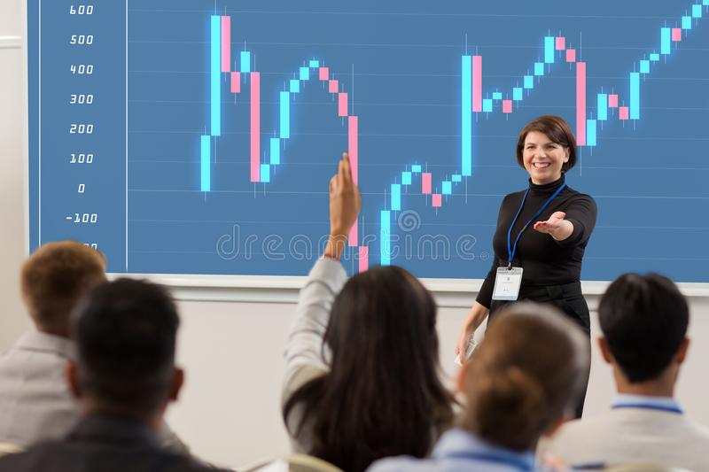 Group of people at business conference or lecture. Business, economy and people concept - smiling businesswoman or financier with forex chart on projection royalty free stock photos