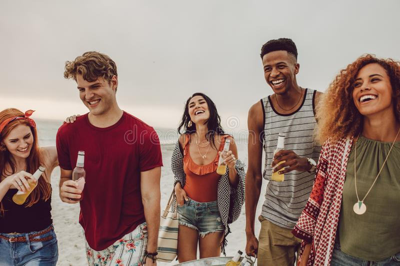 Multi-ethnic friends enjoying at the beach. Group of people carrying beverage tub for party on beach. Diverse group of young people walking outdoors and having royalty free stock photos