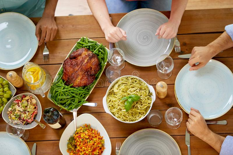 Group of people with chicken and pasta on table. Thanksgiving day, eating and leisure concept - group of people having roast chicken or turkey and pasta for royalty free stock image