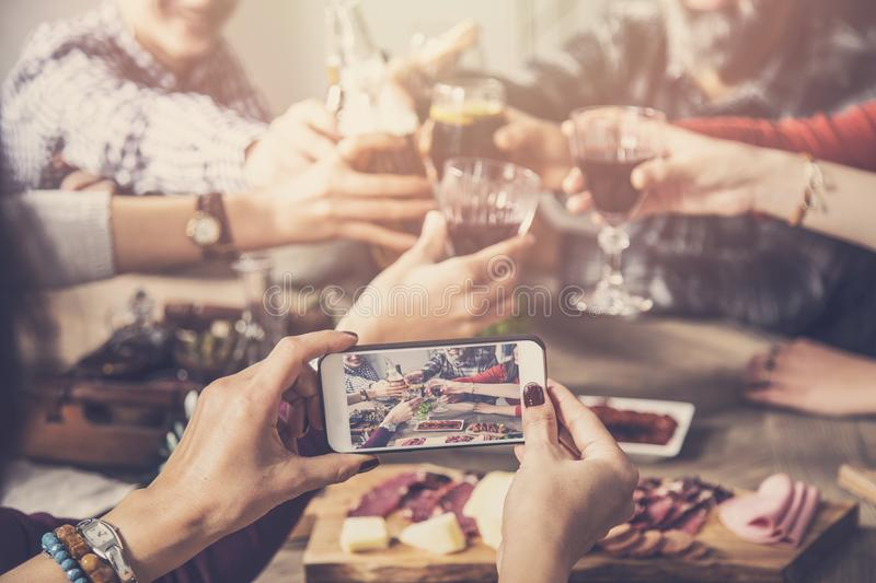 Group of people clinking drinks and taking photo royalty free stock images