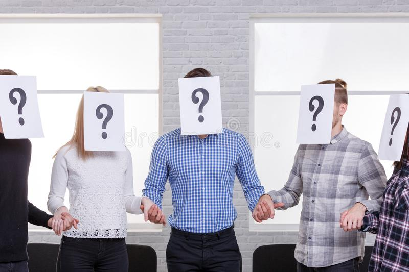 A group of people with closed faces sheets with a question mark holding hands. Stand in a semicircle in the room stock photography