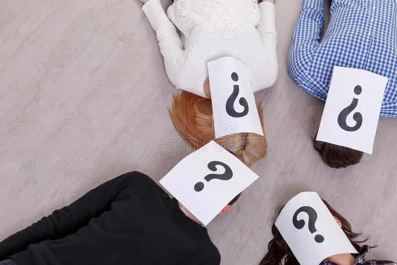 A group of people with closed faces with a question mark on the floor. A group of people with closed faces sheets with a question mark are lying on the floor in royalty free stock photo