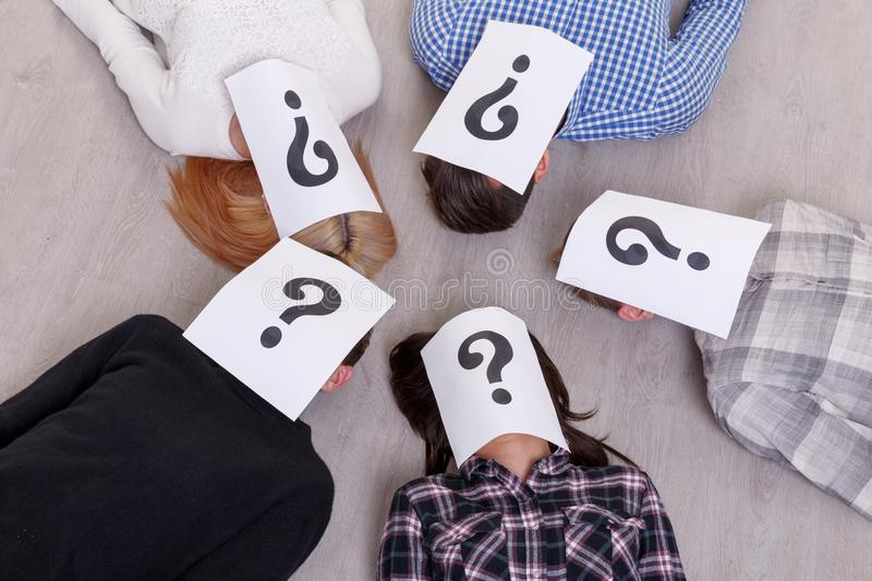 A group of people with closed faces sheets with a question mark lie on the floor of five people close-up. A group of people with closed faces with sheets with a stock image