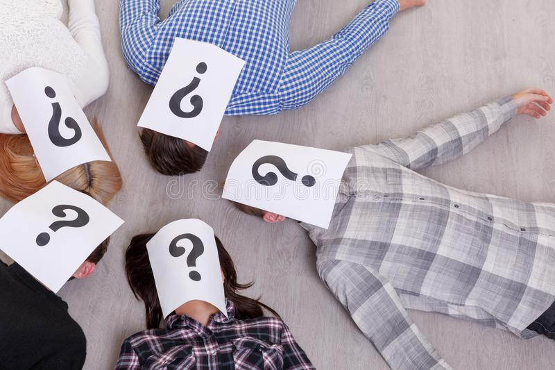 A group of people with closed faces with a question mark on the floor on the left. A group of people with closed faces sheets with a question mark are lying on stock images