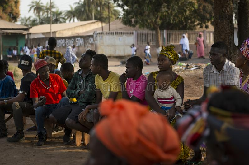 Group of people at a community reunion in the Bissaque neighbourhood in the city of Bissau, Guinea Bissau. Bissau, Republic of Guinea-Bissau - January 29, 2018 royalty free stock photo