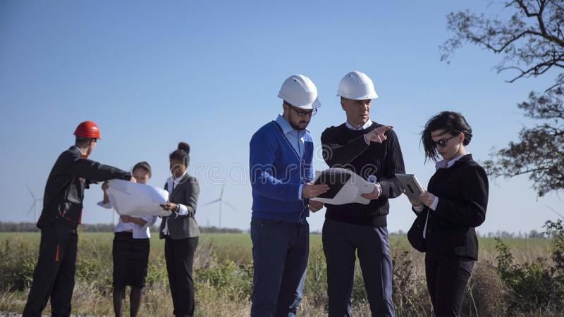 Group of people creating wind turbines project royalty free stock images