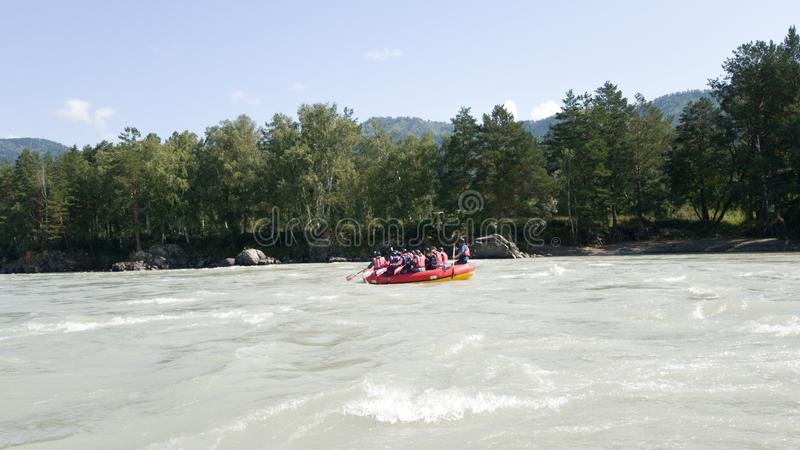 A group of people descends in a raft on the Katun river in Altai. Active vacation in nature. Sports weekend royalty free stock photography