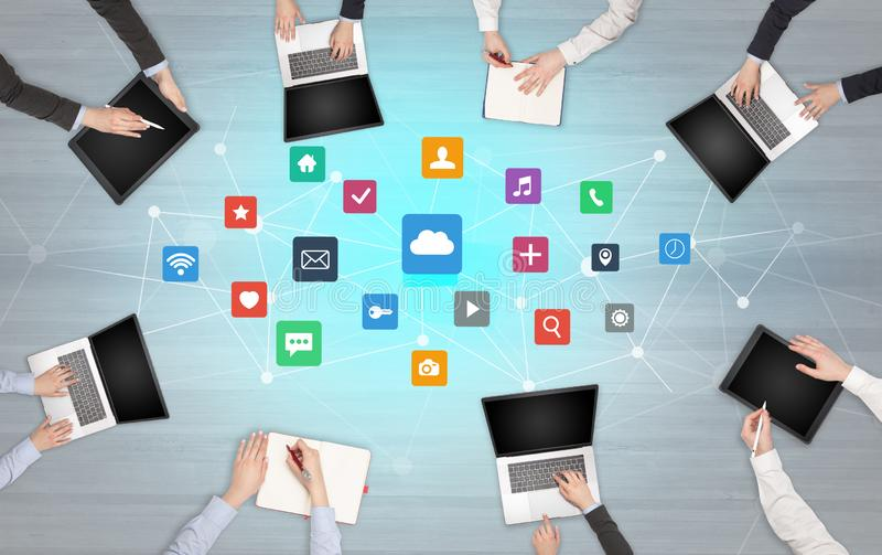 Group of people with devices in hands working on laptops and tablets. Group of people with devices in hands working in team on tablets, laptops with application royalty free stock image
