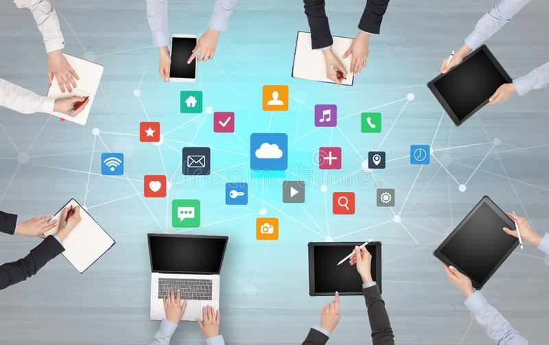 Group of people with devices in hands working on laptops and tablets. Group of people with devices in hands working in team on tablets, laptops with application stock photos