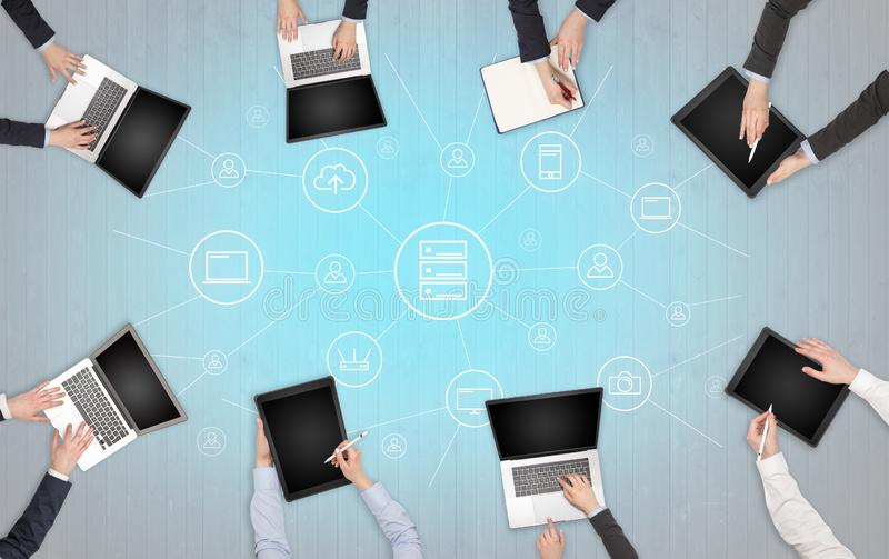 Group of people with devices in hands working on laptops and tablets with office concept. Group of people with devices in hands working in team on tablets royalty free stock image