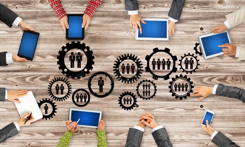 Top view of businesspeople sitting at table and using gadgets. Group of people with devices in hands working together as symbol of networking and communication royalty free stock images