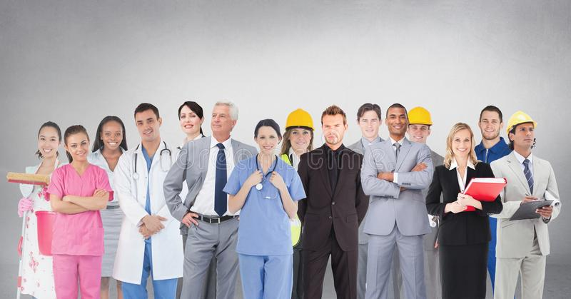 Group of people with different professions standing in front of blank grey background. Digital composite of Group of people with different professions standing stock photo