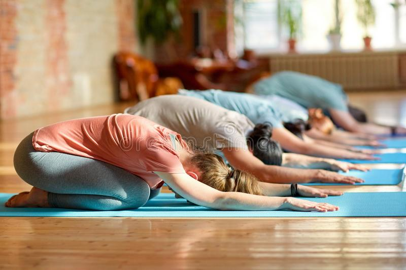 Group of people doing yoga exercises at studio royalty free stock photo