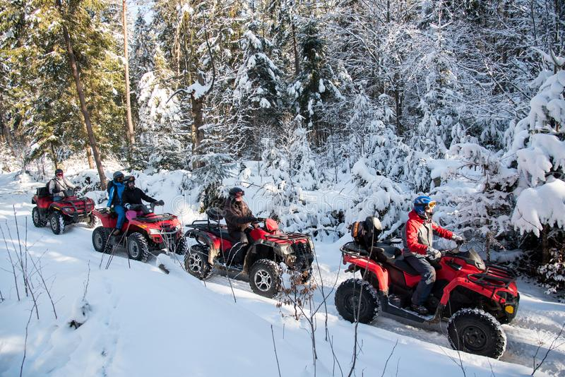 Group of people driving off-road four-wheelers ATV bikes in winter forest. Group of people driving off-road four-wheelers ATV bikes in beautiful winter forest stock photo