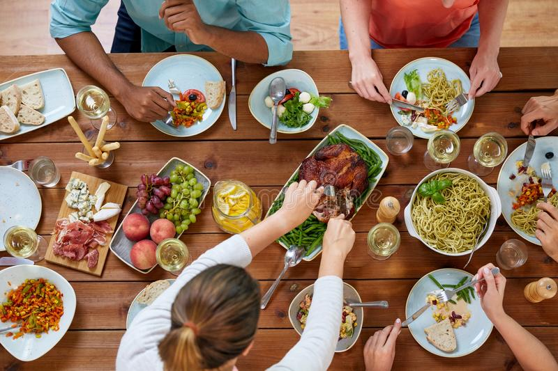 Group of people eating chicken for dinner stock photo