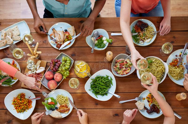 Group of people eating at table with food stock photos