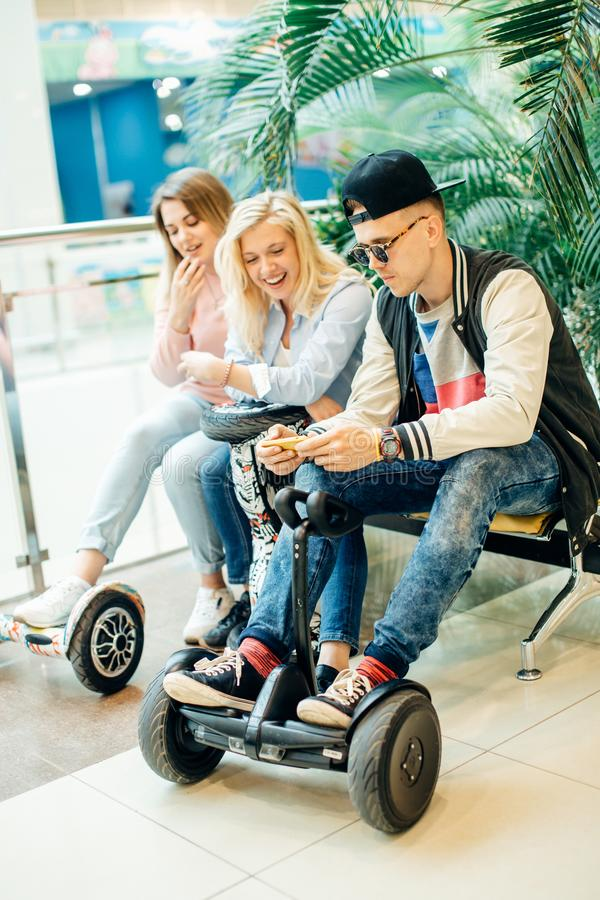 Group of people on electric scooter hoverboard sitting at bench and using phone stock photo