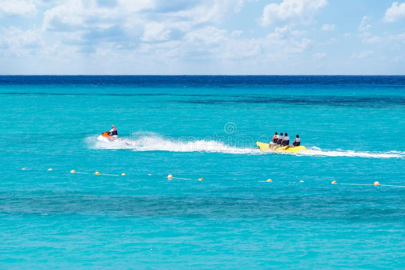 A Group of People Enjoying A Banana Boat Trip Over Blue Ocean Water royalty free stock images