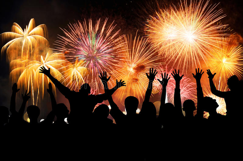 Group of people enjoying spectacular fireworks show in a carnival or holiday. People in silhouette royalty free stock photography