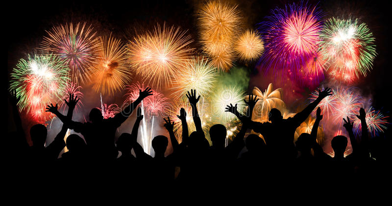 Group of people enjoying spectacular fireworks show in a carnival or holiday. People in silhouette stock image