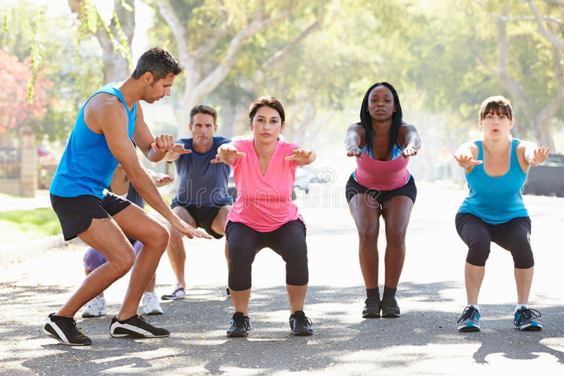 Group Of People Exercising InStreet With Personal Trainer